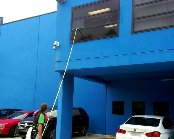 Camden Window Cleaning doing window cleaning with a pole for higher windows at a business in the Ingleburn industrial area